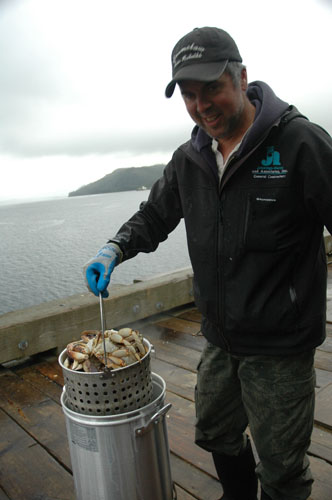 Steve takes fresh crab from the cooker on the dock